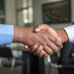 Two business men forming a partnership by shaking hands